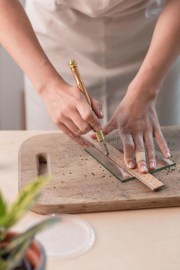 Artist cutting sheets of stained glass into small mosaic squares. Close-up royalty free stock image