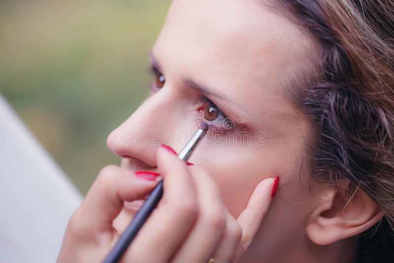 Artist doing professional make up of young beautiful woman royalty free stock photography
