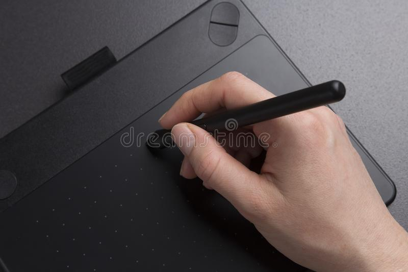 Artist draws on black graphic tablet close-up. designer`s hand with pen on graphic tablet royalty free stock photo
