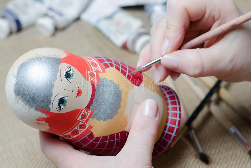 The artist draws a doll-matryoshka. Female hands with a brush close-up royalty free stock photos