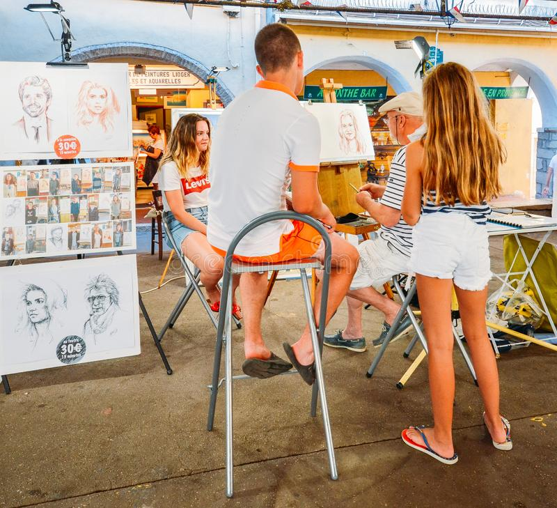 Artist draws a life portrait of tourists at Provencal Market in Antibes, Cote D`Azur, France. Antibes, France - July 8th, 2018: Artist draws a life portrait of royalty free stock photography