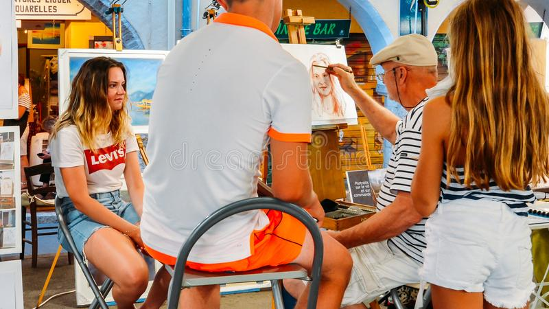 Artist draws a life portrait of tourists at Provencal Market in Antibes, Cote D`Azur, France. Antibes, France - July 8th, 2018: Artist draws a life portrait of stock photo