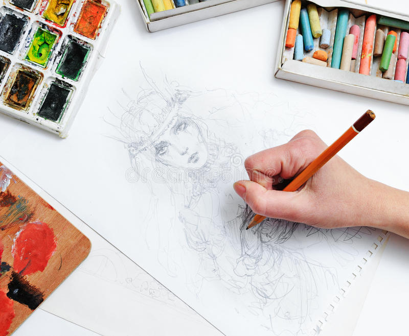 Artist draws sketch. The artist's hand drawing a pencil sketch picture on paper stock photo