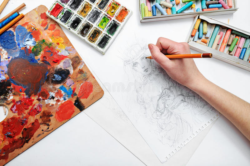Artist draws sketch. The artist's hand drawing a pencil sketch picture on paper stock image