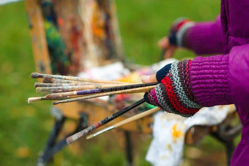 Artist& femelle x27 ; pinceaux de prise de main de s et peinture d'un croquis de photos stock