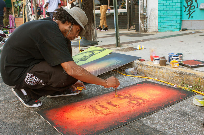 Artist Flicks Yellow Paint Onto Painting At Arts Festival. Atlanta, GA, USA - September 12, 2015: An artist flicks yellow paint onto the painting he's creating stock photos