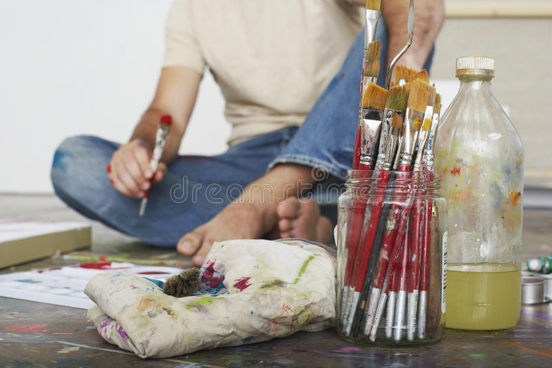 Artist On Floor With Paint Brushes And Materials. Low section of a male artist sitting on floor with paint brushes and materials stock photography