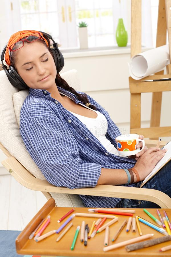 Artist girl enjoying relaxation. Smiling with eyes closed, headphones on, drinking coffee, colorful pencil drawing stock image