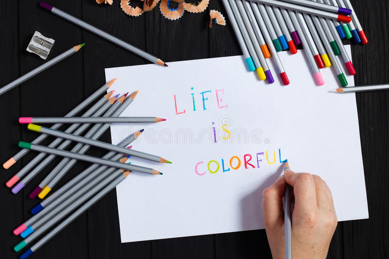 Artist hand with color pencil and sheet of paper. Painter holding pencil for writing life is colorful text. Art, workshop, craft, creativity, inspiration royalty free stock image