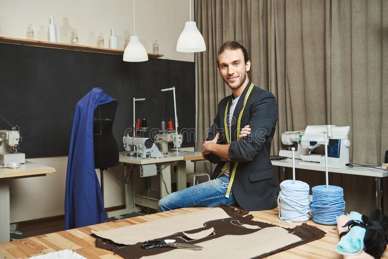 Artist and his work place. Portrait of mature attractive caucasian male clothes designer with stylish hairstyle and royalty free stock image