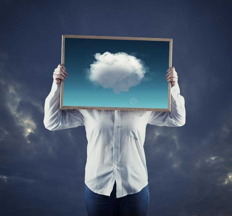 Artist holding an picture with hot air balloons flying away from the frame , on a dramatic sky in background. The concept of stock photos