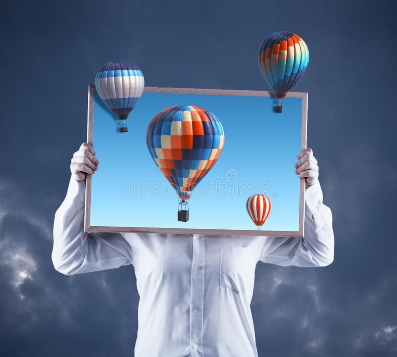 Artist holding an picture with hot air balloons royalty free stock images