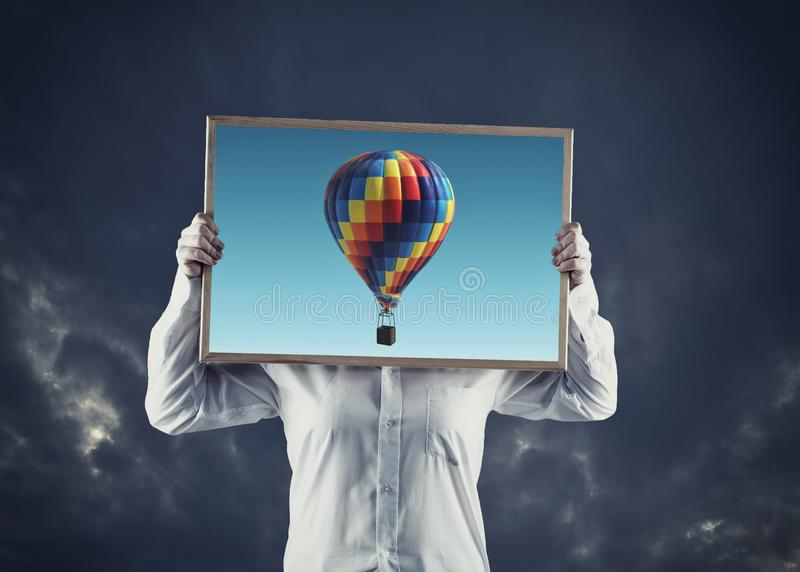 Artist holding an picture with hot air balloons flying, on a dramatic sky in background. The concept of fulfilling desires and stock photos