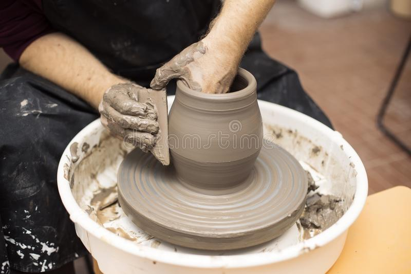 Artist makes clay pottery on a spin wheel. Close up detail view at an artist makes clay pottery on a spin wheel stock photography