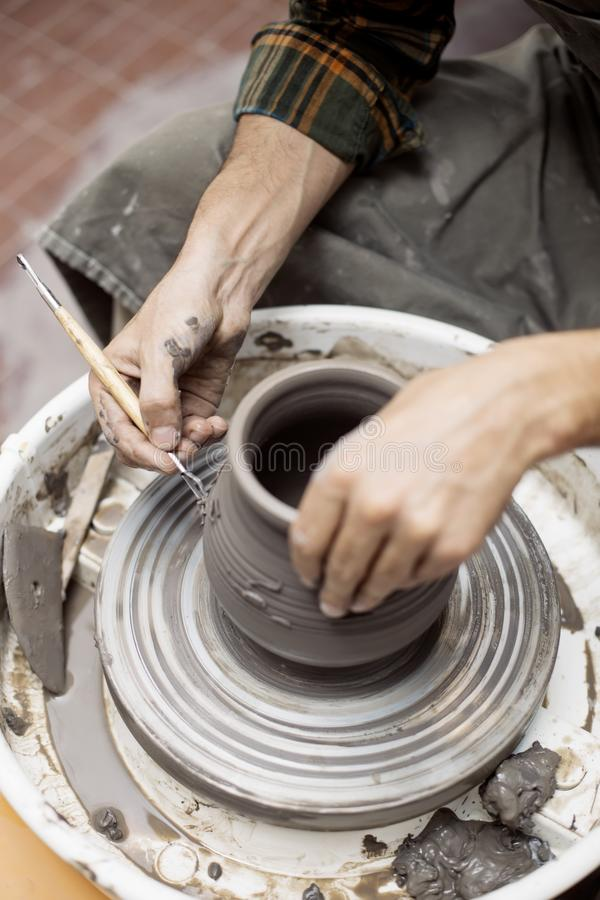 Artist makes clay pottery on a spin wheel. Close up detail view at an artist makes clay pottery on a spin wheel stock photo