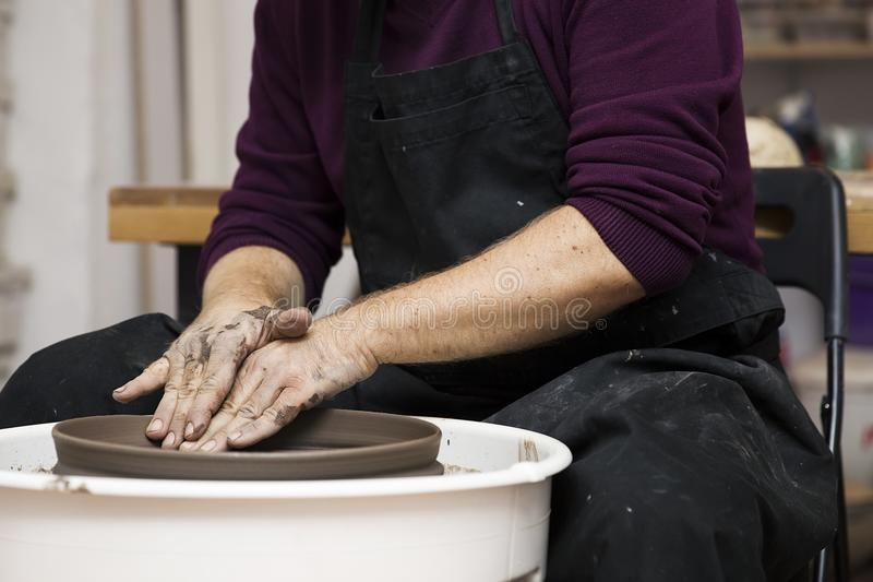 Artist makes clay pottery on a spin wheel. Close up detail view at an artist makes clay pottery on a spin wheel stock image