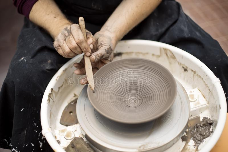 Artist makes clay pottery on a spin wheel. Close up detail view at an artist makes clay pottery on a spin wheel royalty free stock image