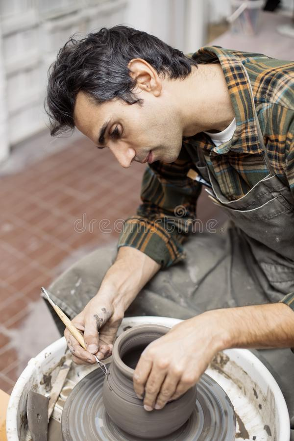 Artist makes clay pottery on a spin wheel. View at an artist makes clay pottery on a spin wheel in workshop stock images