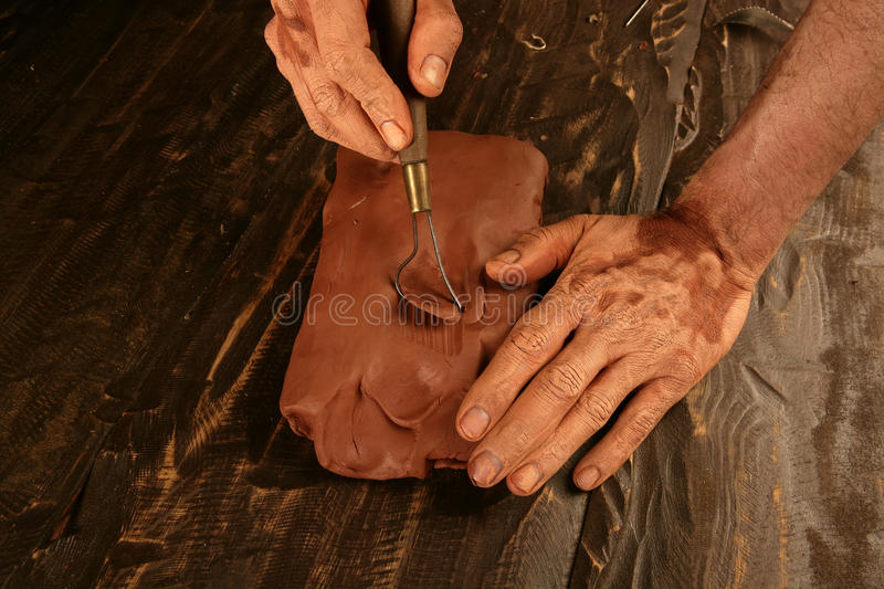 Artist man hands working red clay for handcraft royalty free stock images