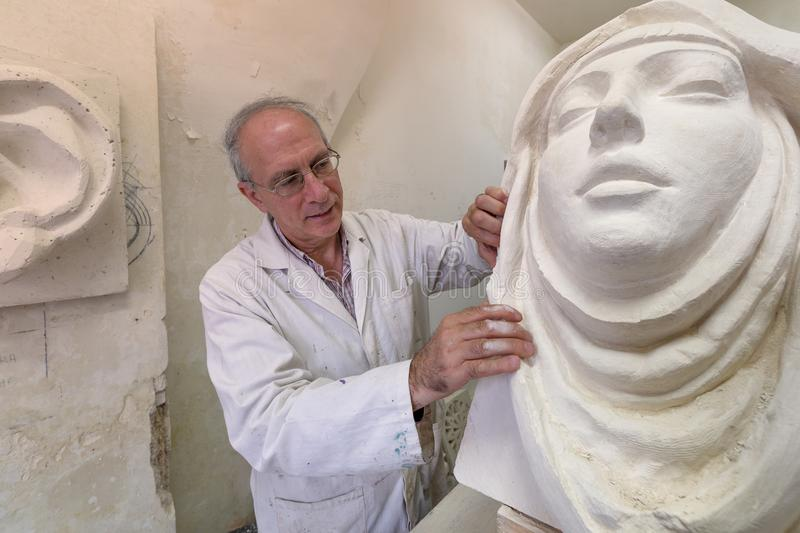 Artist master at work in studio on a sculpture of face stock illustration
