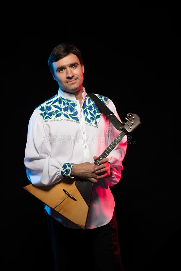 Artist musician A brunette man in a white and blue pattern folk shirt plays a balalaika royalty free stock photography