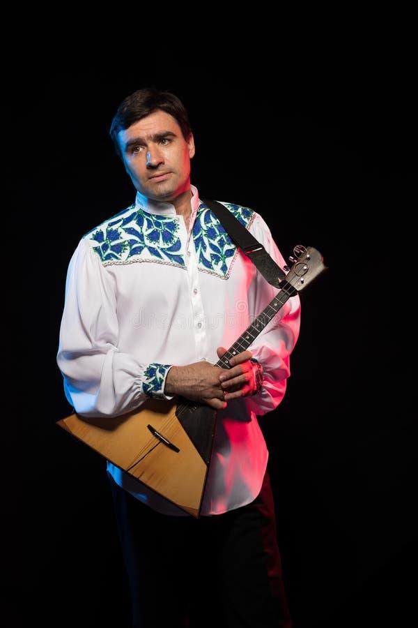 Artist musician A brunette man in a white and blue pattern folk shirt plays a balalaika stock photo