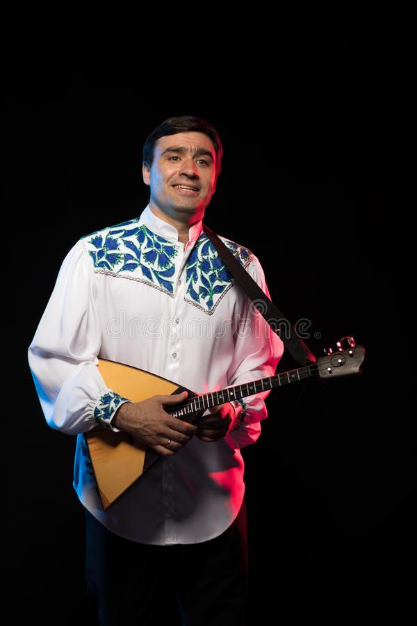 Artist musician A brunette man in a white and blue pattern folk shirt plays a balalaika stock image