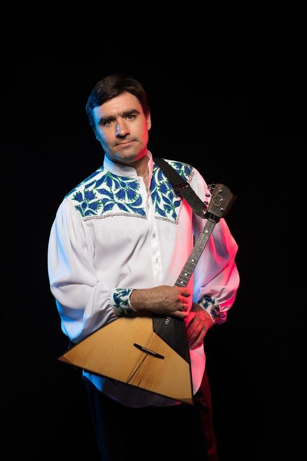 Artist musician A brunette man in a white and blue pattern folk shirt plays a balalaika stock photography