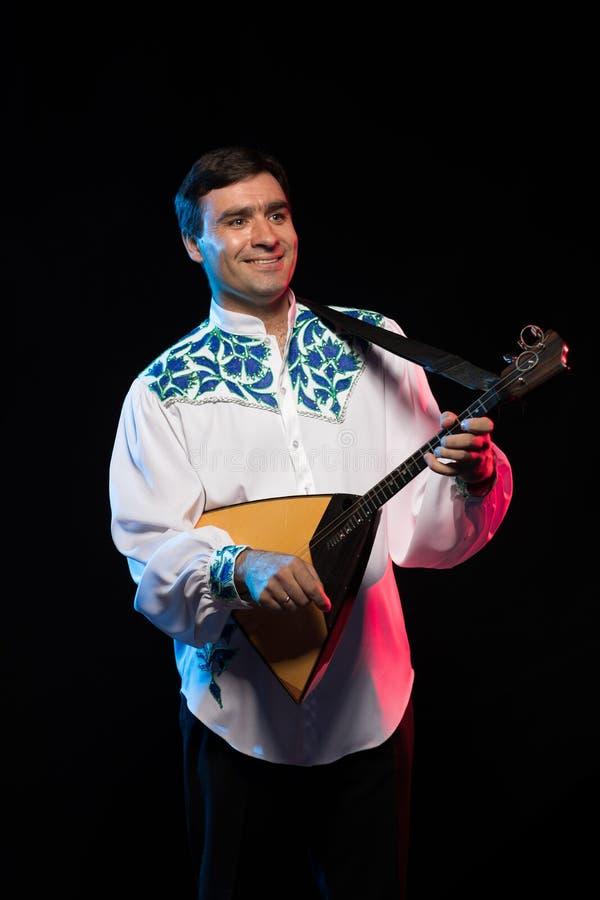 Artist musician A brunette man in a white and blue pattern folk shirt plays a balalaika stock photos