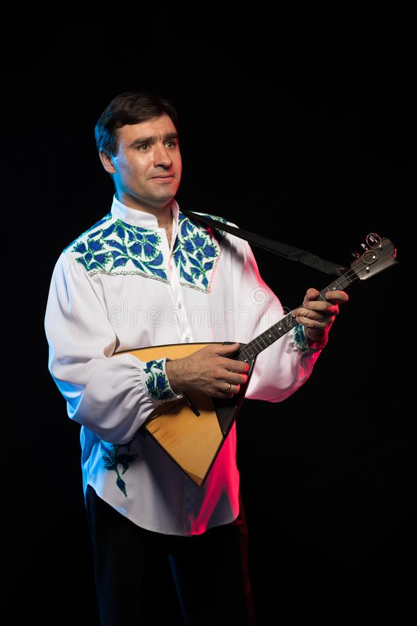 Artist musician A brunette man in a white and blue pattern folk shirt plays a balalaika royalty free stock image
