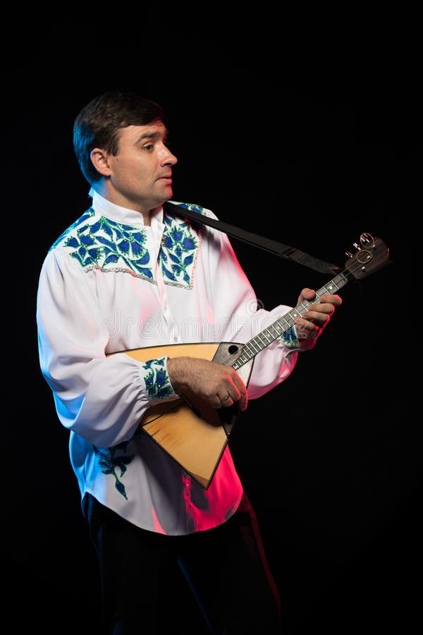 Artist musician A brunette man in a white and blue pattern folk shirt plays a balalaika royalty free stock photo