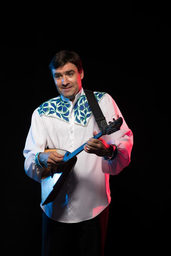 Artist musician A brunette man in a white and blue pattern folk shirt plays a balalaika royalty free stock photos