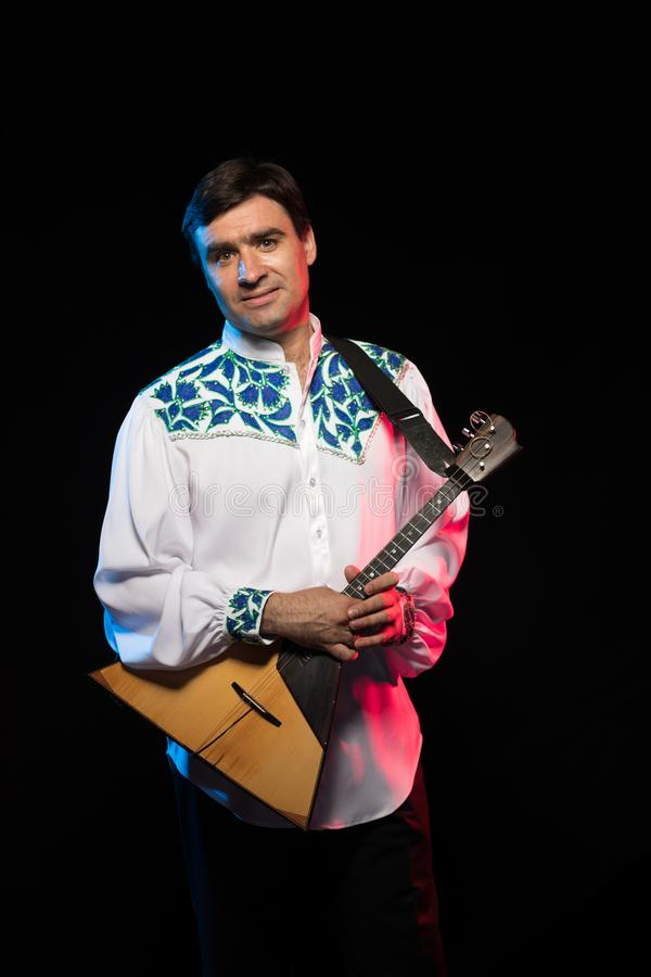 Artist musician A brunette man in a white and blue pattern folk shirt plays a balalaika royalty free stock images