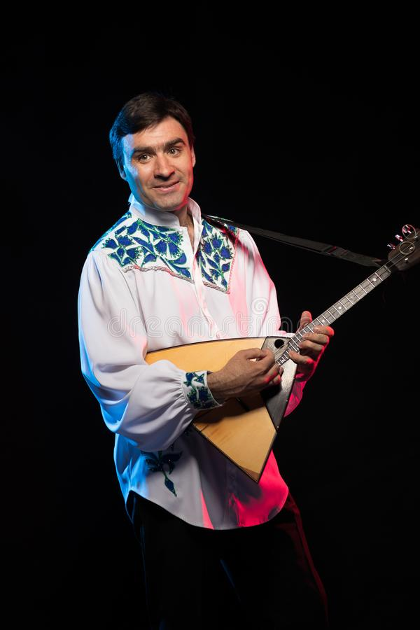 Artist musician A brunette man in a white and blue pattern folk shirt plays a balalaika stock photo