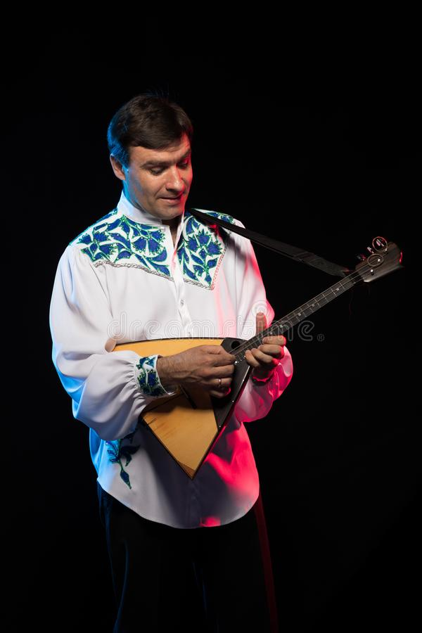 Artist musician A brunette man in a white and blue pattern folk shirt plays a balalaika stock image