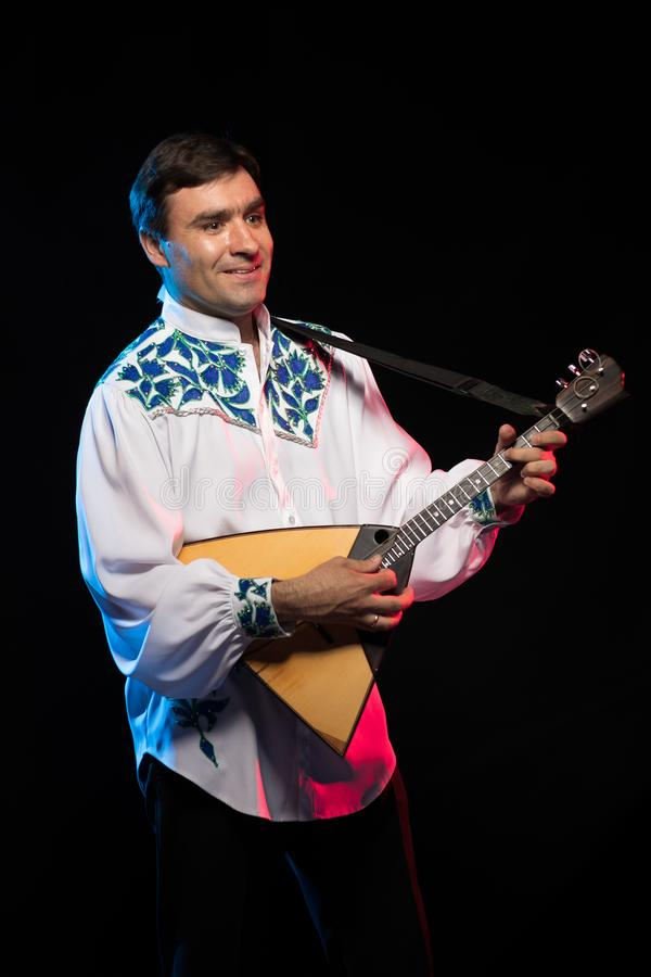 Artist musician A brunette man in a white and blue pattern folk shirt plays a balalaika stock photos