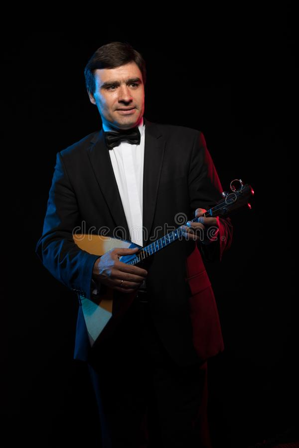 Artist musician, a dark-haired man in a black suit and a bow tie, plays a balalaika stock photo