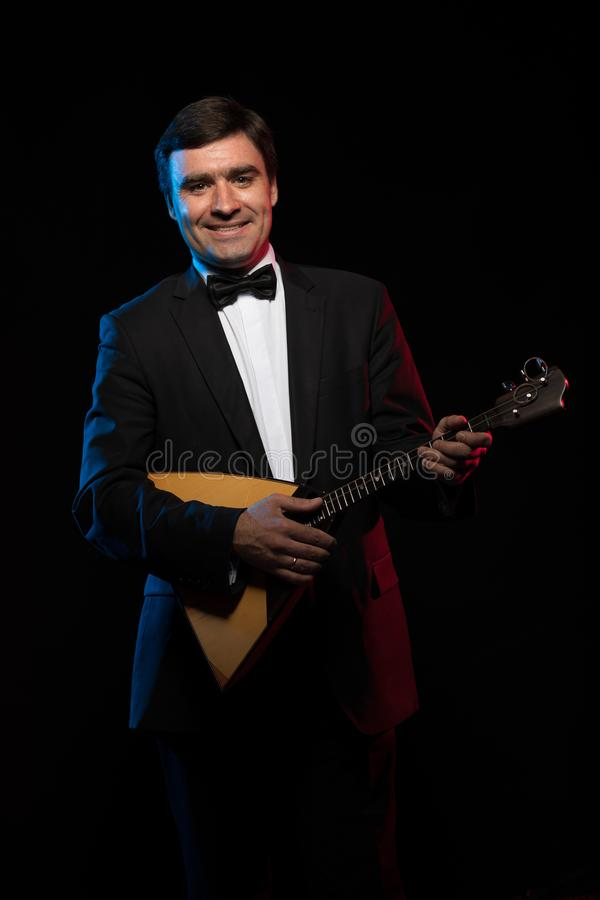 Artist musician, a dark-haired man in a black suit and a bow tie, plays a balalaika stock images