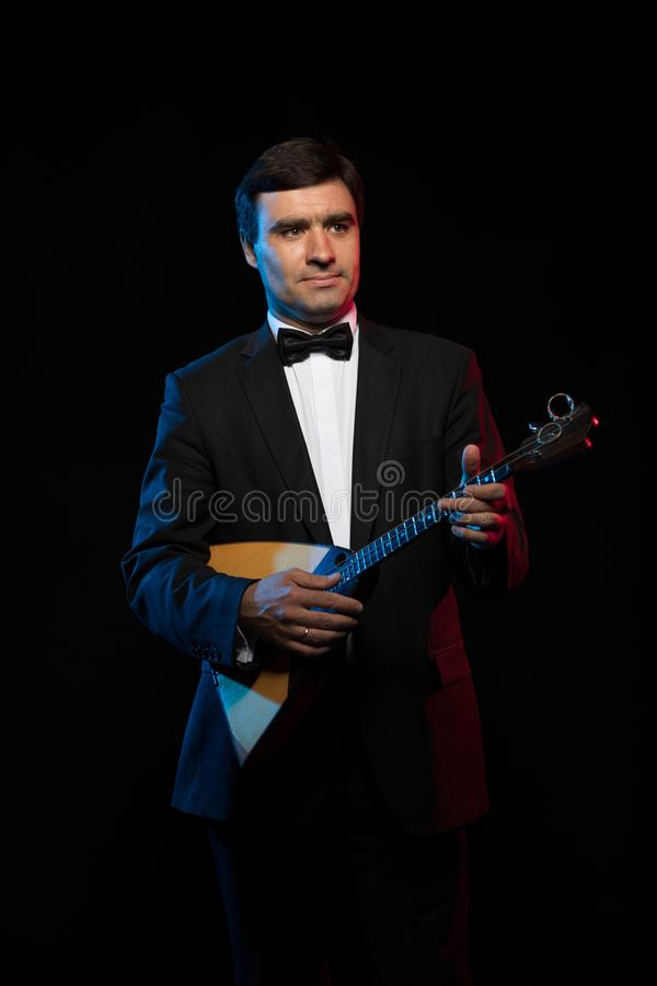 Artist musician, a dark-haired man in a black suit and a bow tie, plays a balalaika stock photography