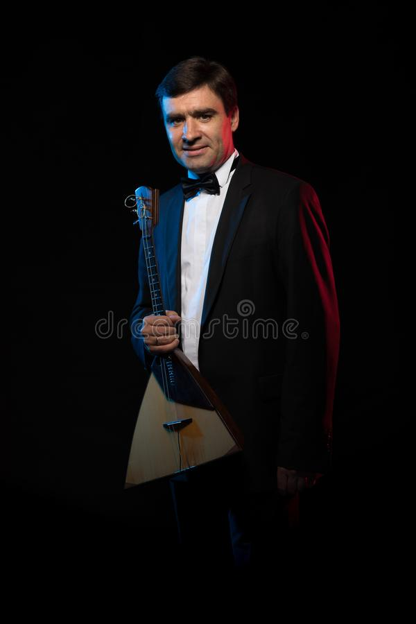 Artist musician, a dark-haired man in a black suit and a bow tie, plays a balalaika stock image
