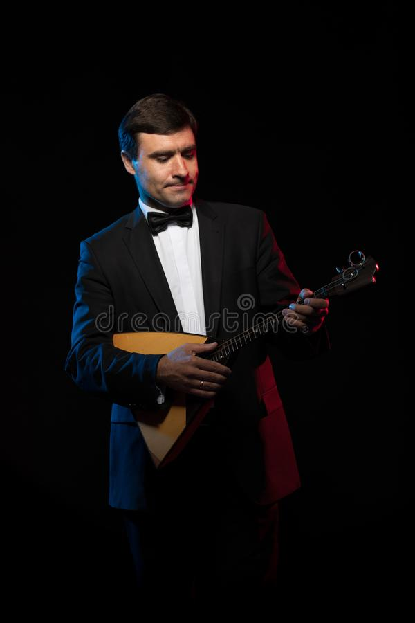 Artist musician, a dark-haired man in a black suit and a bow tie, plays a balalaika royalty free stock image