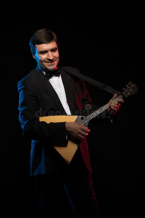 Artist musician, a dark-haired man in a black suit and a bow tie, plays a balalaika stock photos