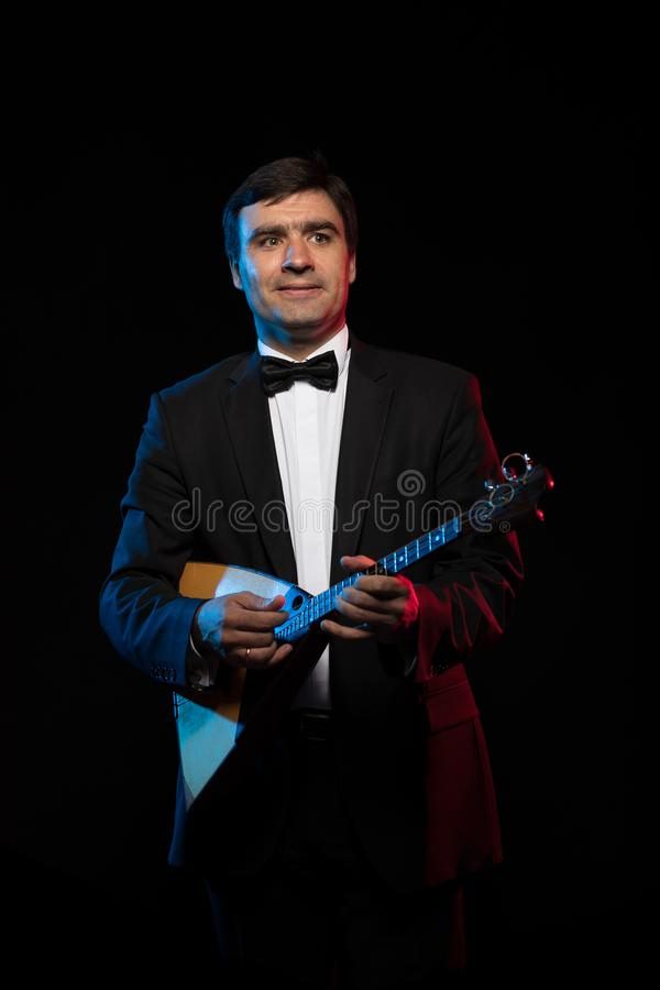 Artist musician, a dark-haired man in a black suit and a bow tie, plays a balalaika royalty free stock photo