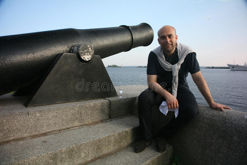 Artist opera singer Aldo Caputo, tenor, italian opera star. Behind the scenes. On the front of the Kronstadt quay at the historic antique guns, artillery stock image