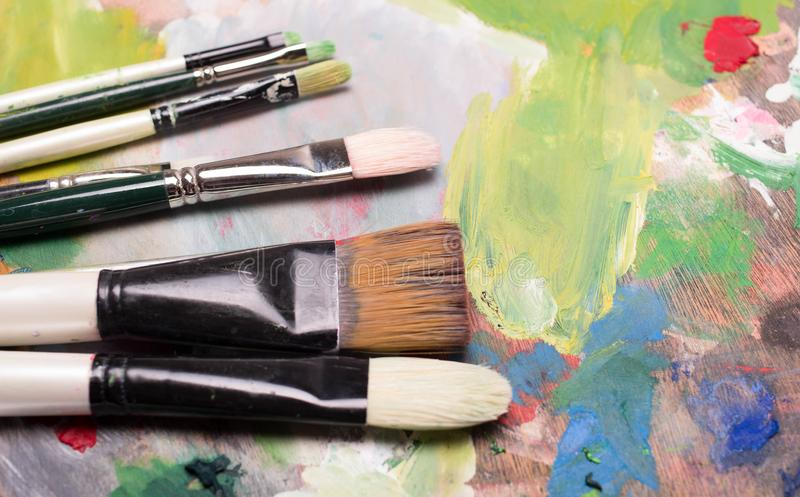 Artist paint brushes and oil paint on wooden artistic palette b royalty free stock photos