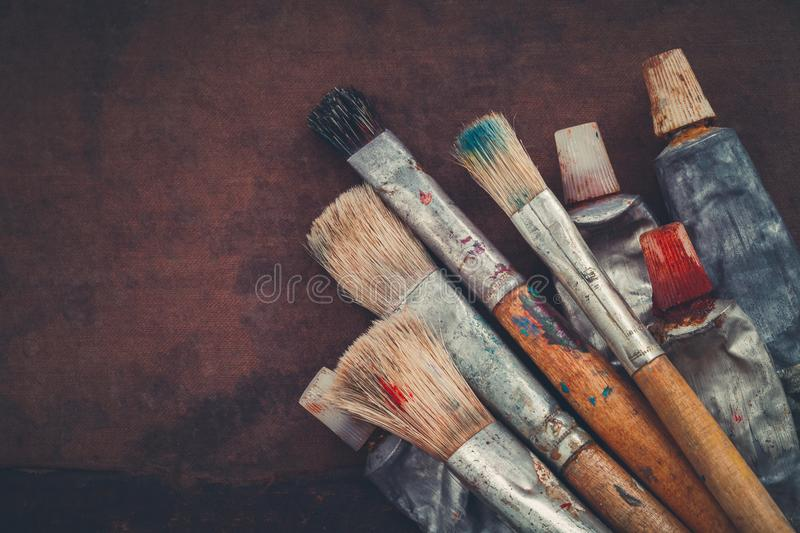 Artist paintbrushes, paint tubes closeup on brown canvas background. stock image