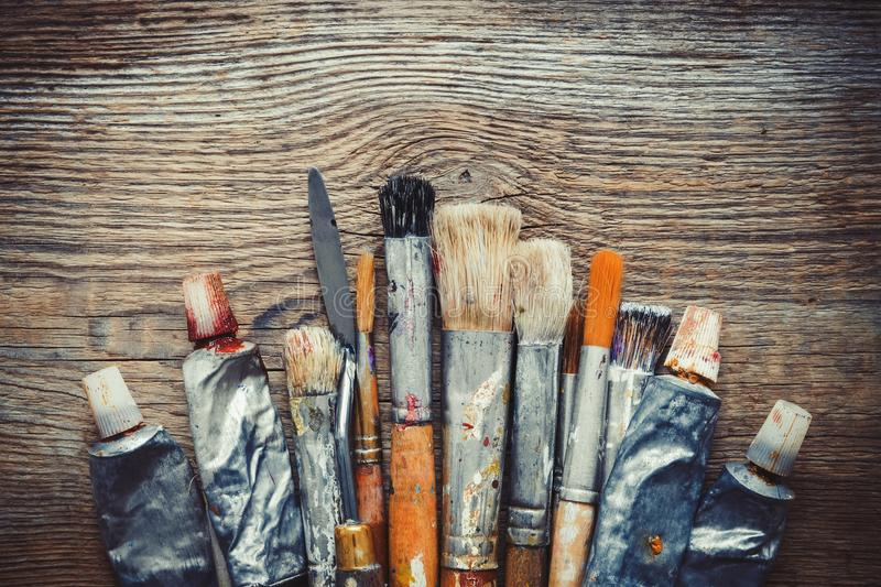 Artist paintbrushes, paint tubes and palette knife closeup. Artist paintbrushes, paint tubes and palette knife closeup on old wooden background, retro stylized royalty free stock photo