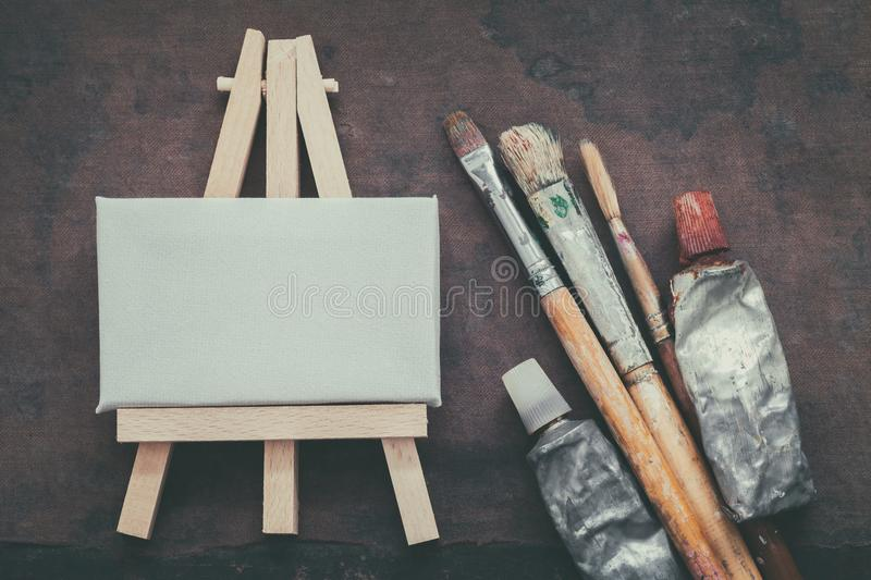 Artist paintbrushes, paint tubes and small easel with canvas closeup. Top view. stock photos