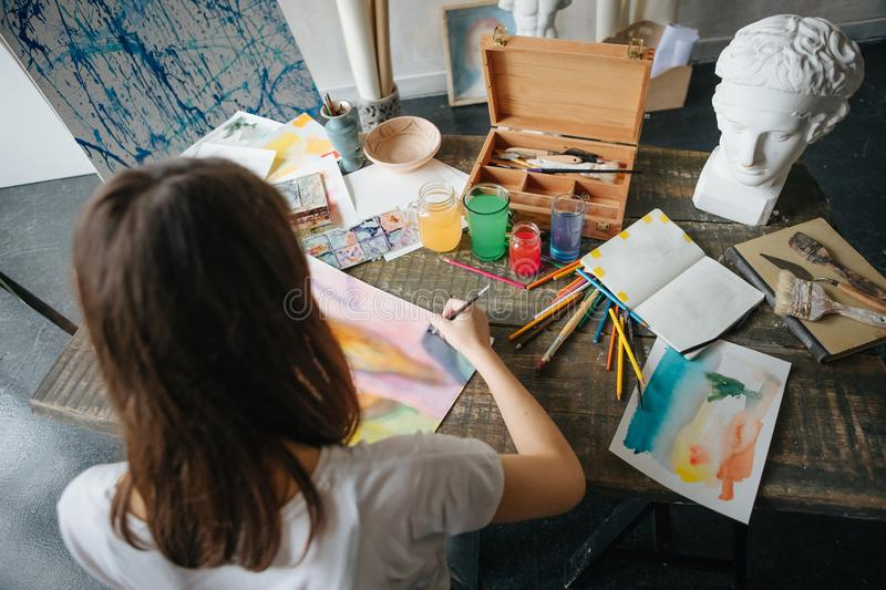 Artist painter young beautiful girl. Working creating process. painting on easel. inspired work. Horizontal composition. Top view from above to work desk stock photos