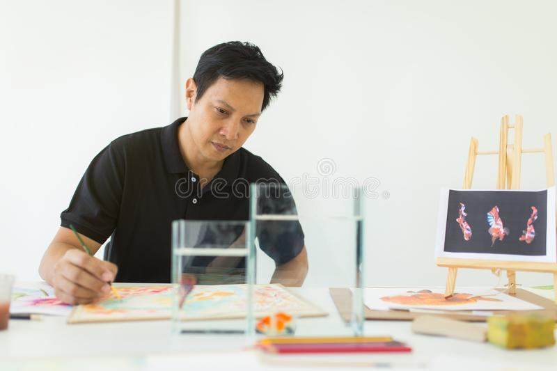 Artist painting artwork at workspace , fish inspiration royalty free stock photos
